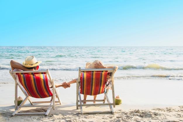 Ontspan het paar bepaalt op strandchiarrie met overzeese golf - de man en de vrouw hebben concept van de vakantie het op zee aard Gratis Foto