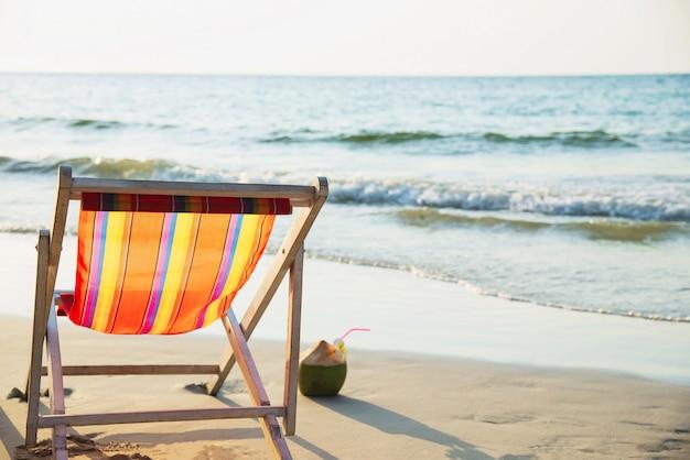 Ontspan ligstoel met verse kokosnoot op schoon zandstrand met blauwe overzees en duidelijke hemel - de overzeese aard ontspant concept Gratis Foto