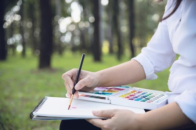 Ontspan vrouw het schilderen het kunstwerk van de waterverfkunst in groene tuin bosaard Gratis Foto