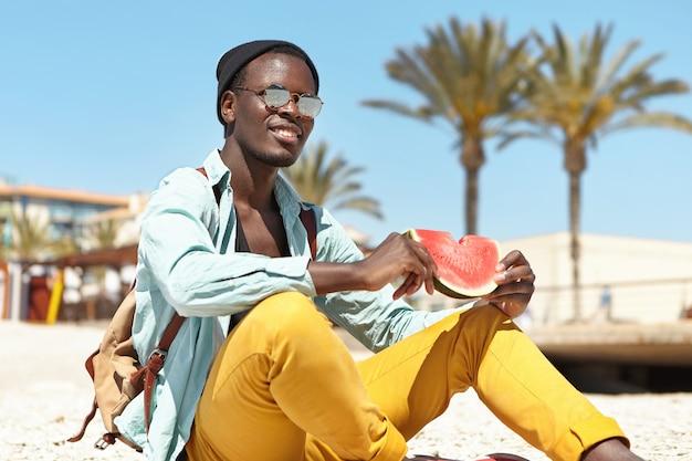Ontspannen avonturier die verse rijpe watermeloen eet Gratis Foto