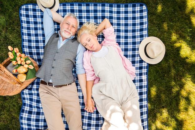 Ontspannen bejaard paar die op het gras leggen Gratis Foto