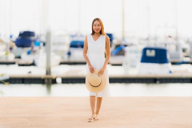 Ontspannen de gelukkige jonge aziatische vrouw van de vrouwenvrije tijd ontspant rond jachthaven Gratis Foto