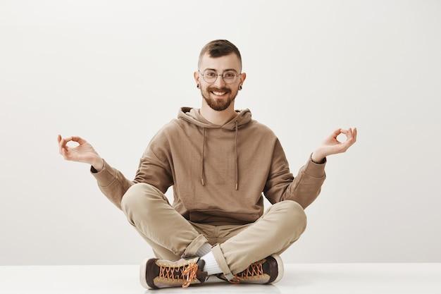 Ontspannen gelukkige hipster-man zit op de vloer en mediteert, blijf kalm Gratis Foto