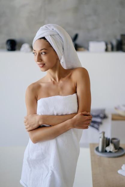 Ontspannen jong kaukasisch vrouwelijk model in witte handdoek, voelt zich verfrist na het nemen van een douche, heeft een gezonde, schone, zachte huid, vormt in een gezellige badkamer. concept voor vrouwen, schoonheid en hygiëne. Gratis Foto