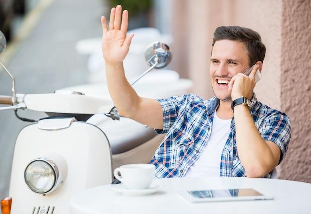 Ontspannen jonge man praten via de telefoon en glimlachen. Premium Foto