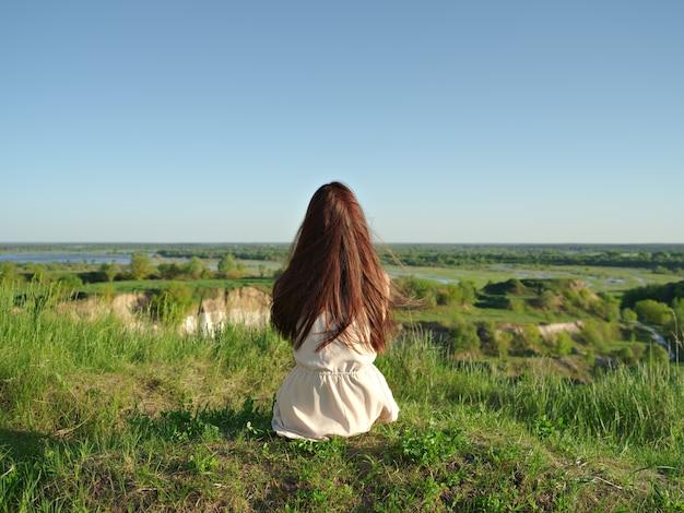 Ontspannen jonge vrouw die uit in het uitzicht kijkt. vreedzaam meisje aanbrengen door een klif die van het landschap geniet. - buitenshuis Gratis Foto