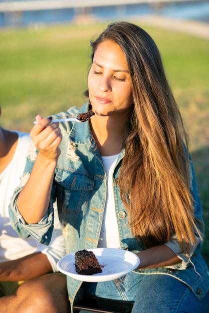 Ontspannen kaukasische vrouw die heerlijke cake in park eet. vrolijke jongeren die in park zitten die cake van plastic schotels eten. vrije tijd Gratis Foto