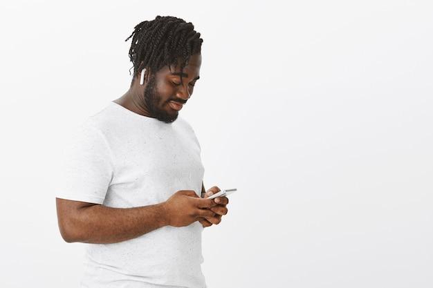 Ontspannen man met vlechten poseren tegen de witte muur met zijn telefoon Gratis Foto