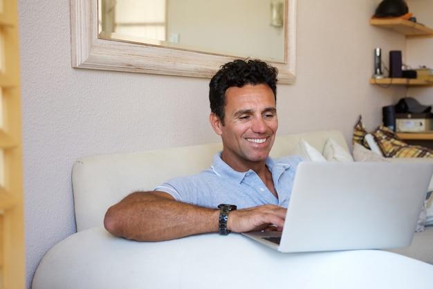 Ontspannen man van middelbare leeftijd lachend met laptop thuis Premium Foto