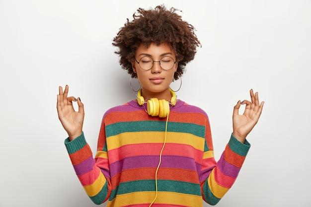 Ontspannen mooie dame met afro-kapsel mediteert binnenshuis, houdt de ogen gesloten, voelt zich tevreden lo luister naar aangename muziek in de koptelefoon, draagt een bril, oorbellen, gestreepte trui. lichaamstaal Gratis Foto
