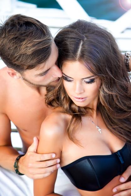 Ontspannen op het strand, vrouw met moderne zwarte top, bronzen zachte huid, make-up op haar mooie gezicht. tender holding Gratis Foto