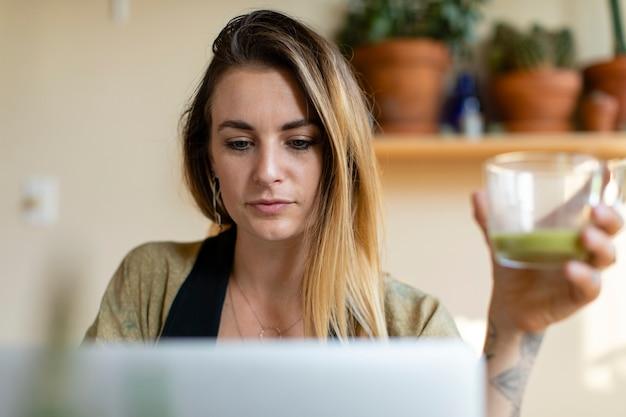 Ontspannen vrouw die van huis aan haar laptop werkt Gratis Foto