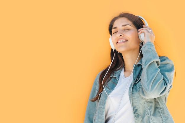 Ontspannen vrouw het luisteren muziek tegen gele achtergrond Gratis Foto