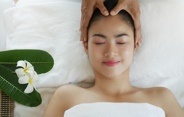 Ontspannende mooie vrouw die een massage voor haar huid op een gezicht in schoonheidssalon hebben Premium Foto