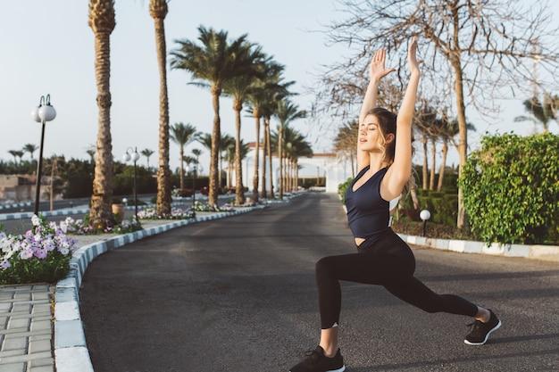 Ontspanning van jonge aantrekkelijke jonge vrouw die zich uitstrekt op straat in tropische stad. resort, training, opgewekte stemming, fitness, yoga, motivatie. Gratis Foto