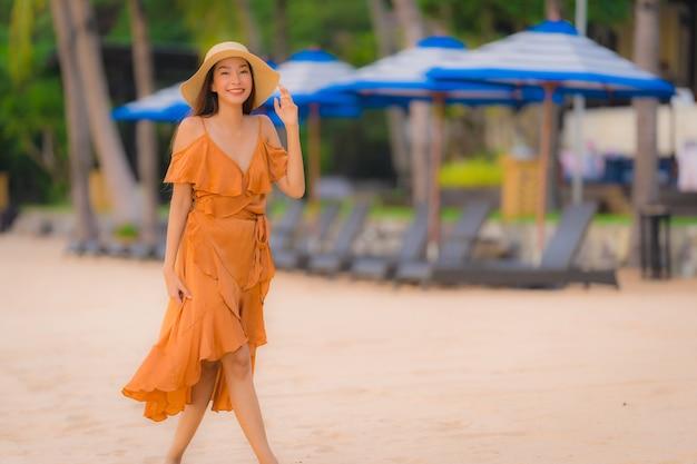 Ontspant de gelukkige jonge glimlach van de portret mooie jonge aziatische vrouw op de strand overzeese oceaan Gratis Foto