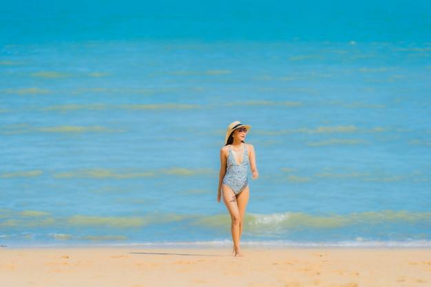 Ontspant de mooie jonge aziatische vrouwen gelukkige glimlach op de tropische strand overzeese oceaan voor vrije tijdsreis Gratis Foto
