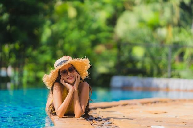 Ontspant de mooie jonge aziatische vrouwen van het portret glimlach en gelukkig rond zwembad in hoteltoevlucht Gratis Foto