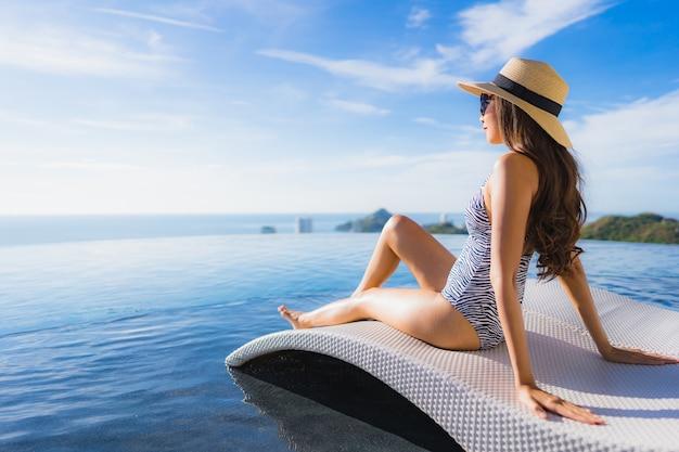Ontspant de mooie jonge aziatische vrouwenglimlach van het portret rond zwembad in hoteltoevlucht voor vrije tijd Gratis Foto