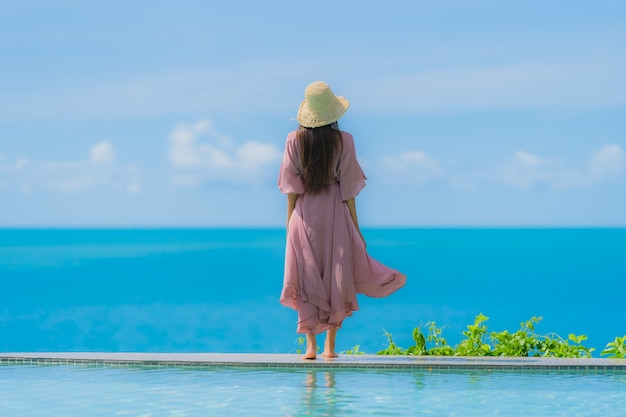 Ontspant de portret jonge aziatische vrouw glimlach gelukkig rond openluchtzwembad in hoteltoevlucht met overzeese oceaanmening Gratis Foto