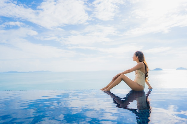 Ontspant de portret jonge aziatische vrouw glimlach gelukkig rond zwembad in hotel en toevlucht Gratis Foto
