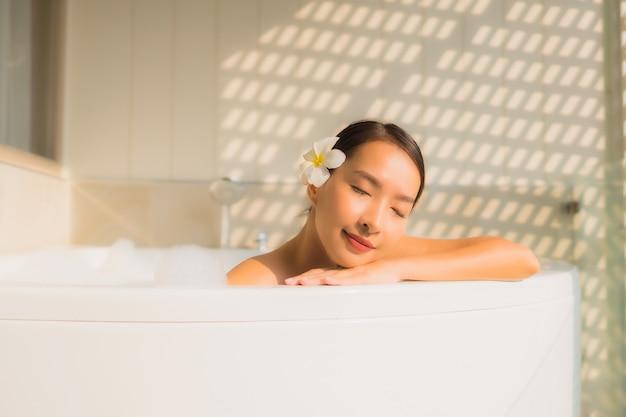 Ontspant de portret jonge aziatische vrouw neemt een bad in badkuip Gratis Foto