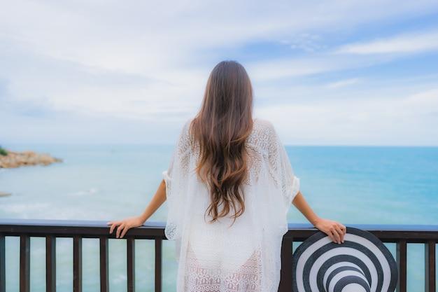 Ontspant de portret mooie jonge aziatische vrouw die overzeese strandoceaan kijken voor in de vakantie van de vakantievakantie Gratis Foto