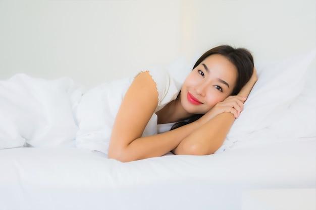 Ontspant de portret mooie jonge aziatische vrouw gelukkige glimlach op bed met witte hoofdkussendeken Gratis Foto