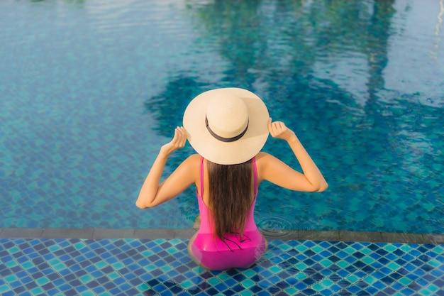 Ontspant de portret mooie jonge aziatische vrouw geniet rond openluchtzwembad in vakantievakantie Gratis Foto
