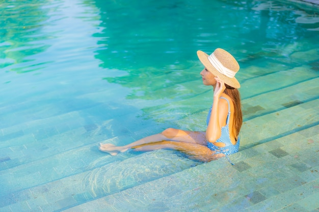 Ontspant de portret mooie jonge aziatische vrouw glimlach geniet van vrije tijd rond zwembad bijna overzees strand oceaanmening op vakantie Gratis Foto