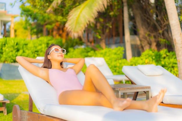 Ontspant de portret mooie jonge aziatische vrouw glimlach geniet van vrije tijd rond zwembad in hoteltoevlucht Gratis Foto