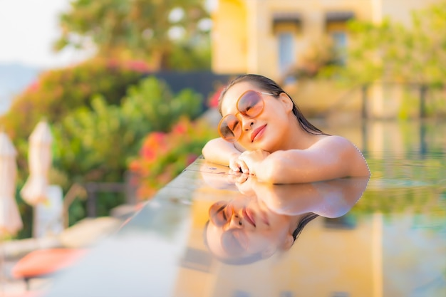 Ontspant de portret mooie jonge aziatische vrouw glimlach geniet van vrije tijd rond zwembad in resorthotel op vakantie Gratis Foto