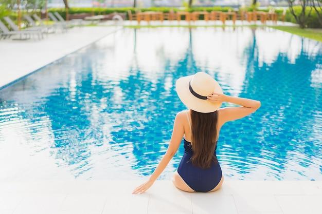 Ontspant de portret mooie jonge aziatische vrouw glimlach rond openluchtzwembad in hoteltoevlucht op vakantiereizen Gratis Foto