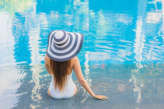 Ontspant de portret mooie jonge aziatische vrouw glimlach rond openluchtzwembad in hoteltoevlucht Gratis Foto
