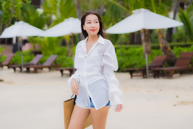 Ontspant de portret mooie jonge aziatische vrouw glimlach rond strand overzeese oceaan in de reisreis van de vakantievakantie Gratis Foto