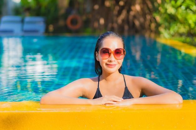 Ontspant de portret mooie jonge aziatische vrouw glimlachvrije tijd rond openluchtzwembad bijna overzees Gratis Foto
