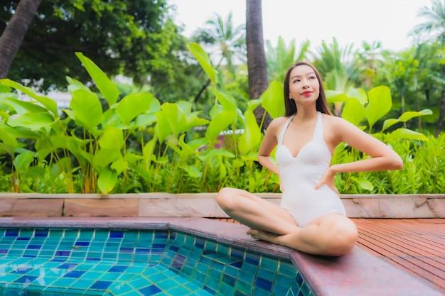 Ontspant de portret mooie jonge aziatische vrouw glimlachvrije tijd rond openluchtzwembad Gratis Foto