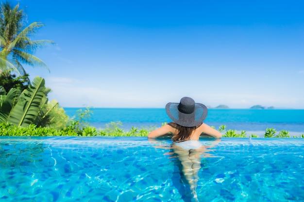 Ontspant de portret mooie jonge aziatische vrouw in luxe openlucht zwembad in bijna het strand overzeese van de hoteltoevlucht oceaan Gratis Foto