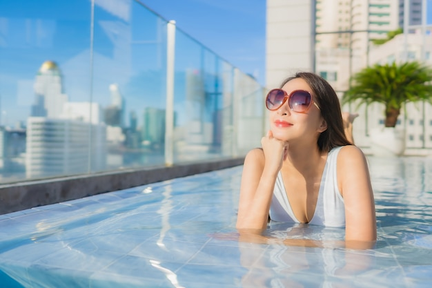 Ontspant de portret mooie jonge aziatische vrouw vrije tijd rond zwembad Gratis Foto