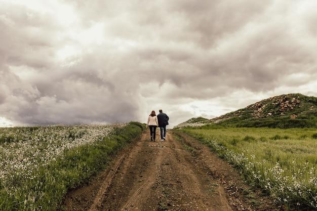 Ontsproten van een mannetje en een wijfje die langs een weg in een vallei met bloemen onder een mistige hemel lopen Gratis Foto