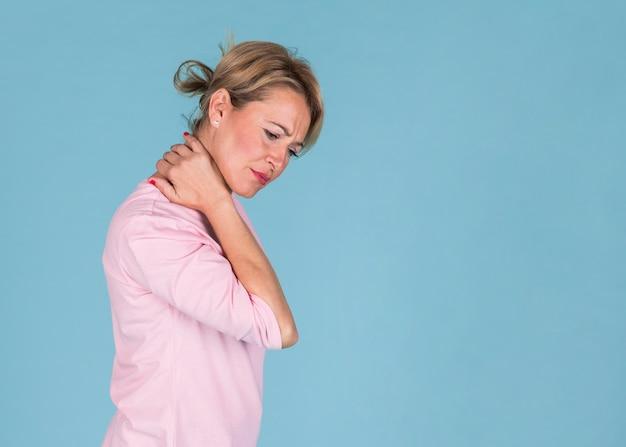Ontstemde vrouw die aan halspijn op blauwe achtergrond lijdt Gratis Foto