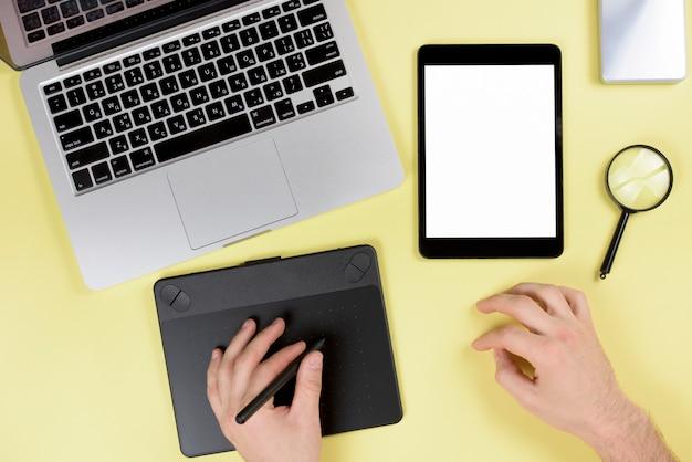 Ontwerper die aan grafische digitale tablet met naald op geel bureau werkt Gratis Foto