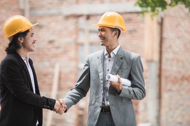 Ontwerpers bespreken bouwplan hand schudden Premium Foto