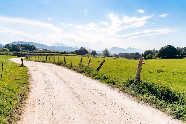 Onverharde weg in het midden van een grasveld onder een blauwe hemel overdag Gratis Foto