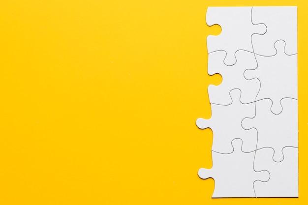 Onvolledige witte puzzelstukjes op gele achtergrond Gratis Foto