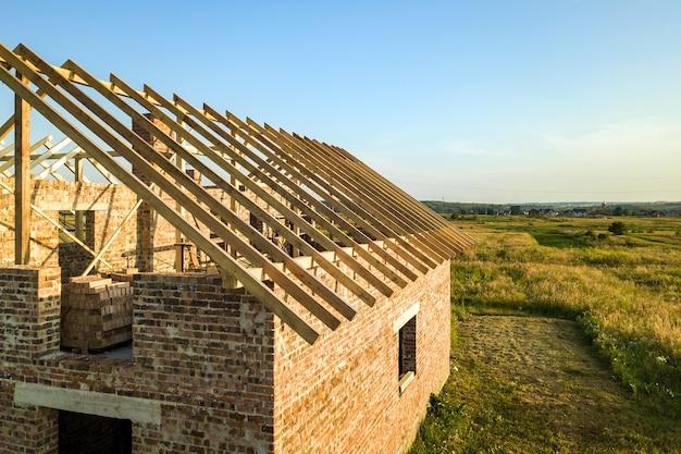 Onvoltooid bakstenen huis met houten dakconstructie in aanbouw. Premium Foto