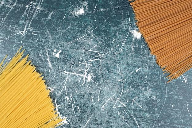 Onvoorbereide deegwarenbos van volkoren spaghetti op marmeren achtergrond Gratis Foto