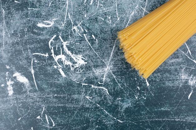 Onvoorbereide deegwarenbos van volkoren spaghetti vastgebonden met touw op marmeren backgroundto Gratis Foto
