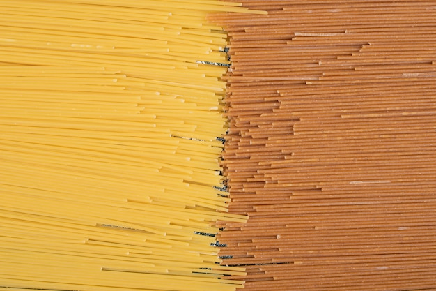 Onvoorbereide verse bruine en gele pasta op marmeren achtergrond. hoge kwaliteit foto Gratis Foto