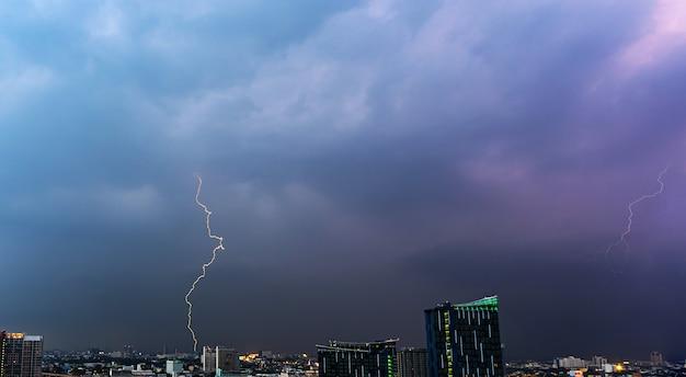 Onweersbuibliksem over de stad bij zonsondergang Premium Foto
